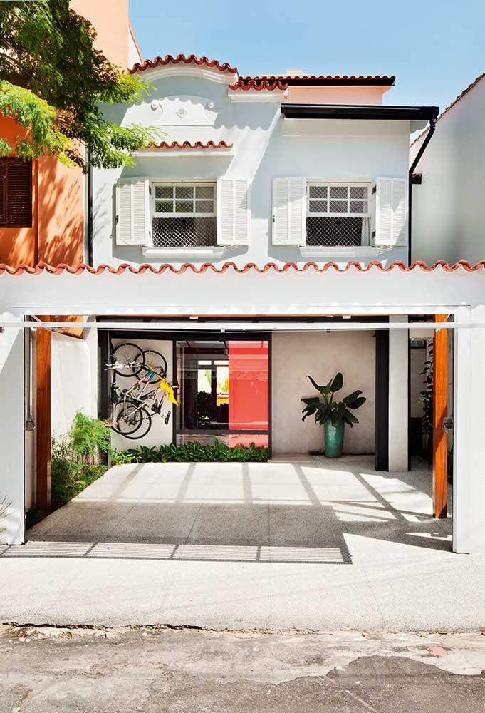 Fachada de casa popular com garagem e espaço para guardar bicicletas