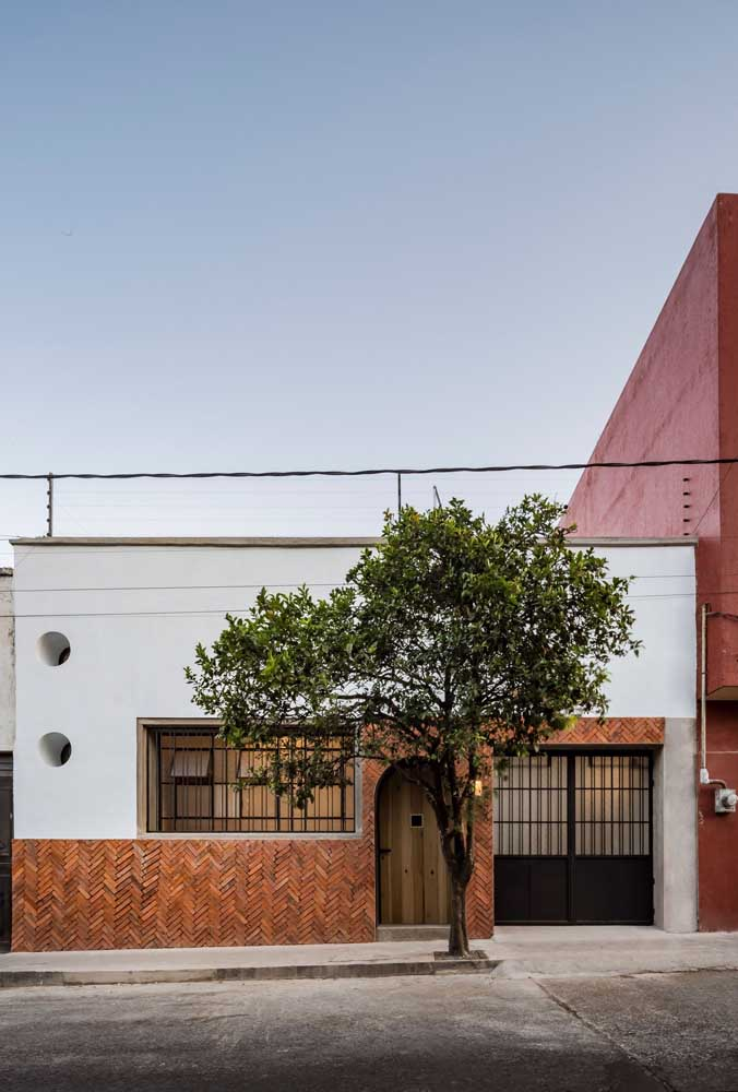 Aqui, o muro baixa revela a arquitetura moderna da fachada da casa popular