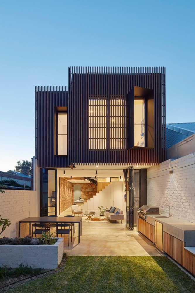 Fachada dos fundos da casa: churrasqueira, gramado e integração com a área interna