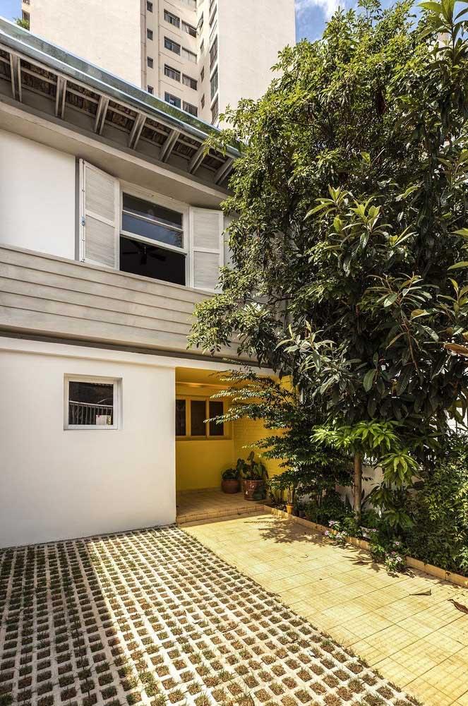 Fachada de casa popular com garagem aberta e pisograma