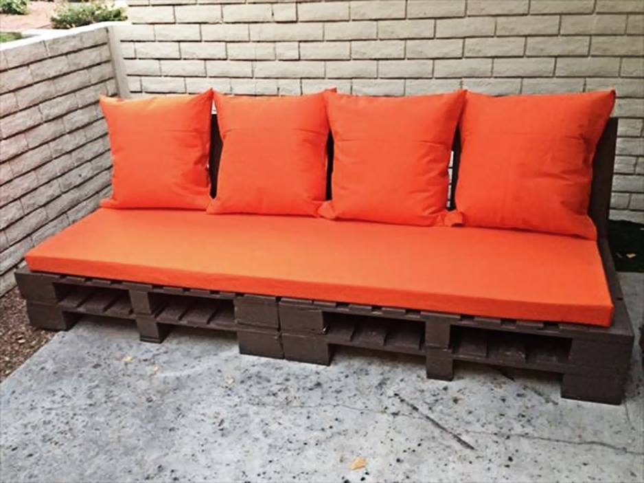 Sofá de pallet marrom com almofadas vermelhas