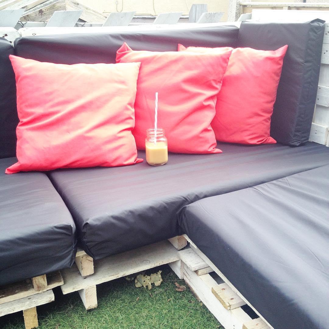 Sofá de pallet com almofadas pretas e vermelhas