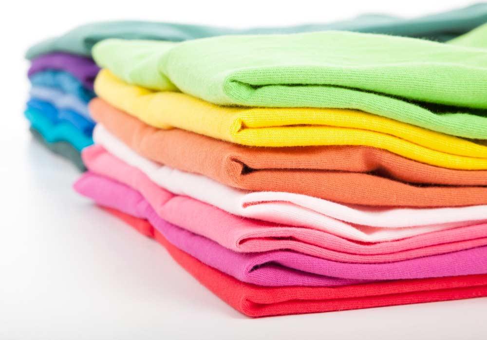 Roupas dobradas e separadas por cor