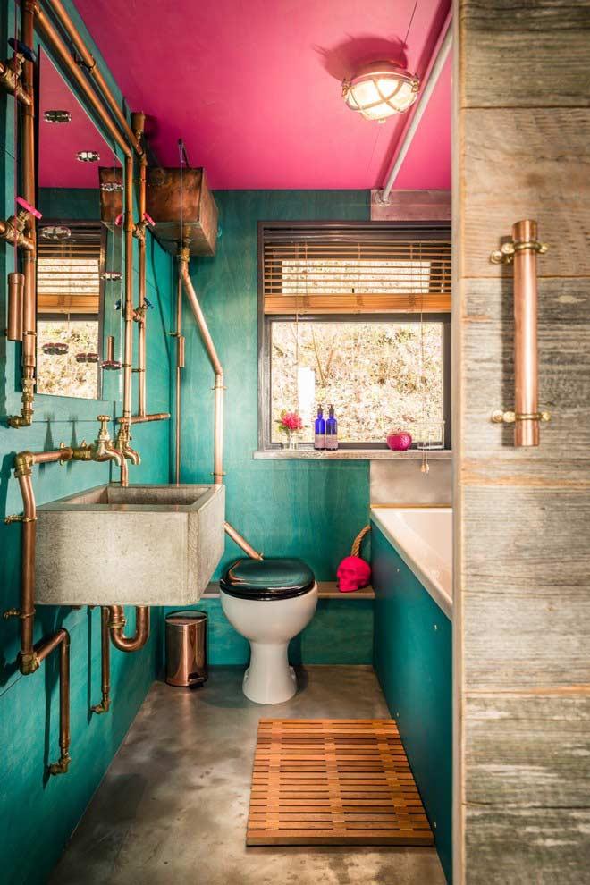 Banheiro pequeno com tubulação aparente