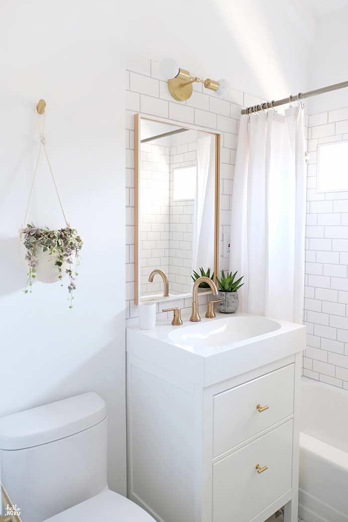 Banheiro pequeno com plantinha na pia e pendente também!