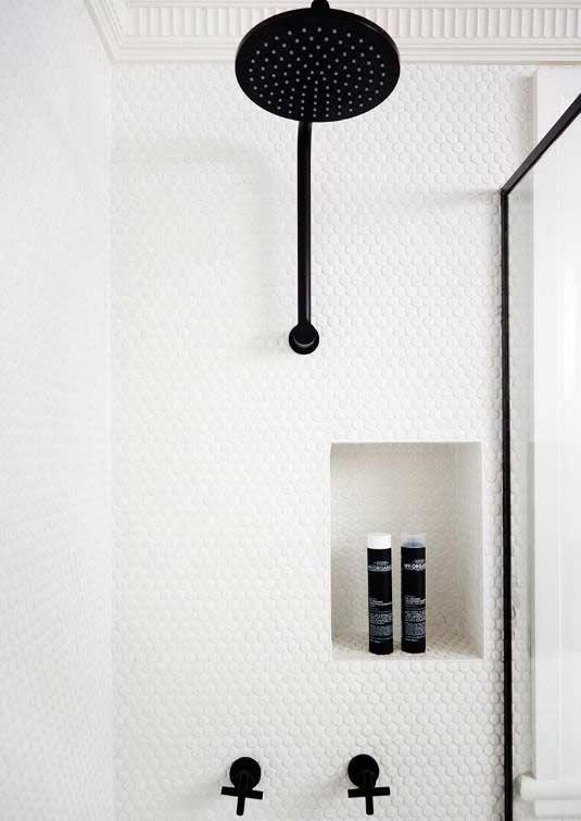Pastilhas brancas pequenas em banheiro com decoração preto e branca