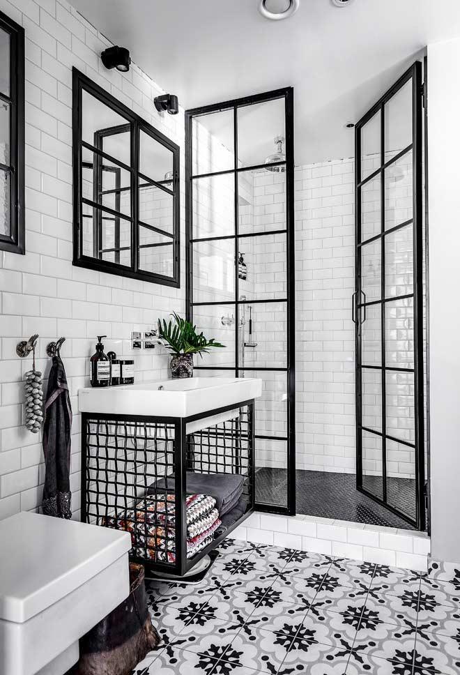 Ladrilho hidráulico e pastilhas subway tiles em banheiro preto e branco