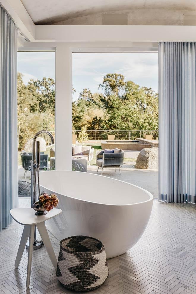 Banheiro com banheira e vista para varanda