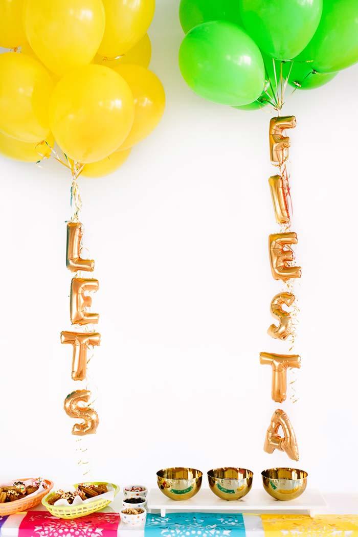 Balões segurando letreiro da festa