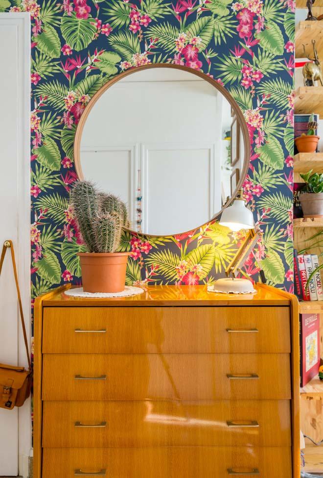 Um vaso com cactos combinando com o papel de parede em tropical