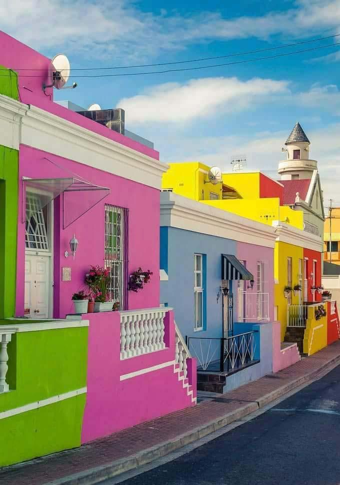 Uma rua de casas com cores cítricas vibrantes