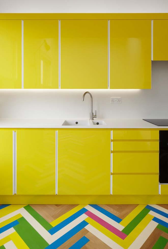 cozinha amarela e branca com piso de madeira