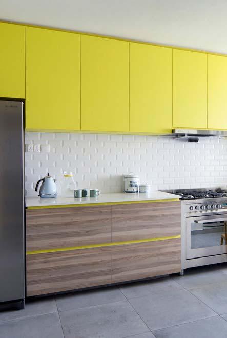 Um tom de amarelo cítrico chamando a atenção nos armários suspensos dessa cozinha