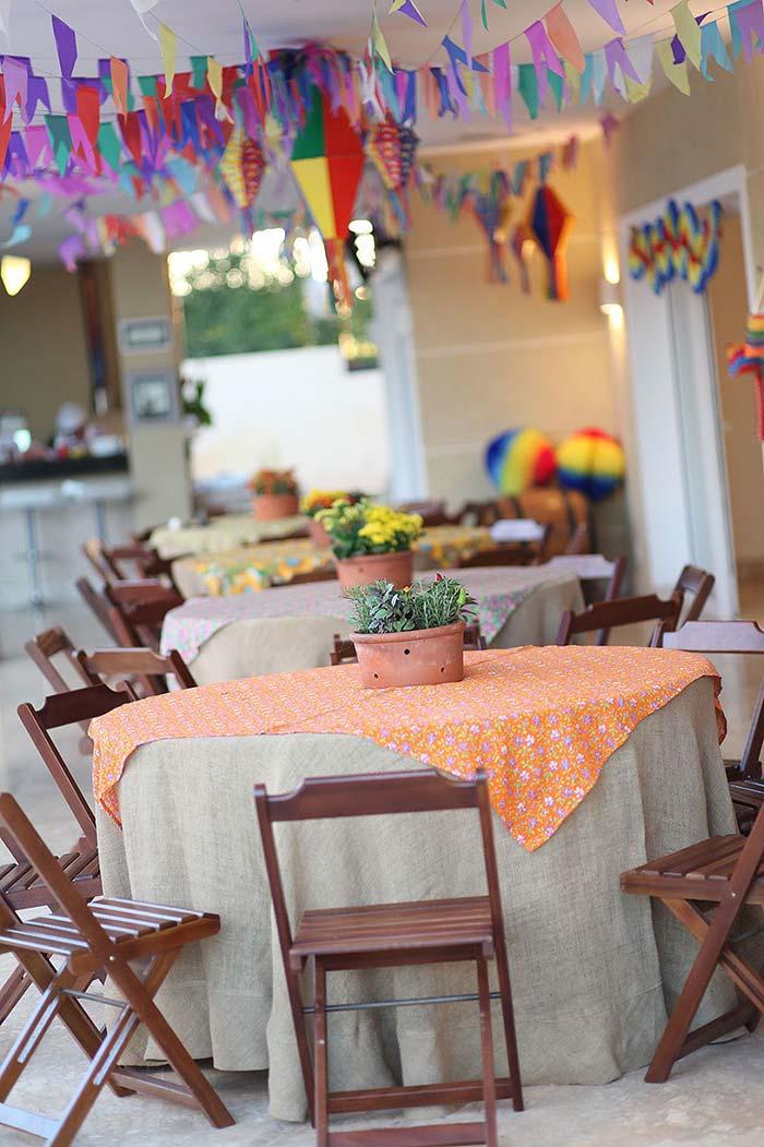 Muitas bandeirinhas para decorar o teto; o vaso de barro decora as mesas