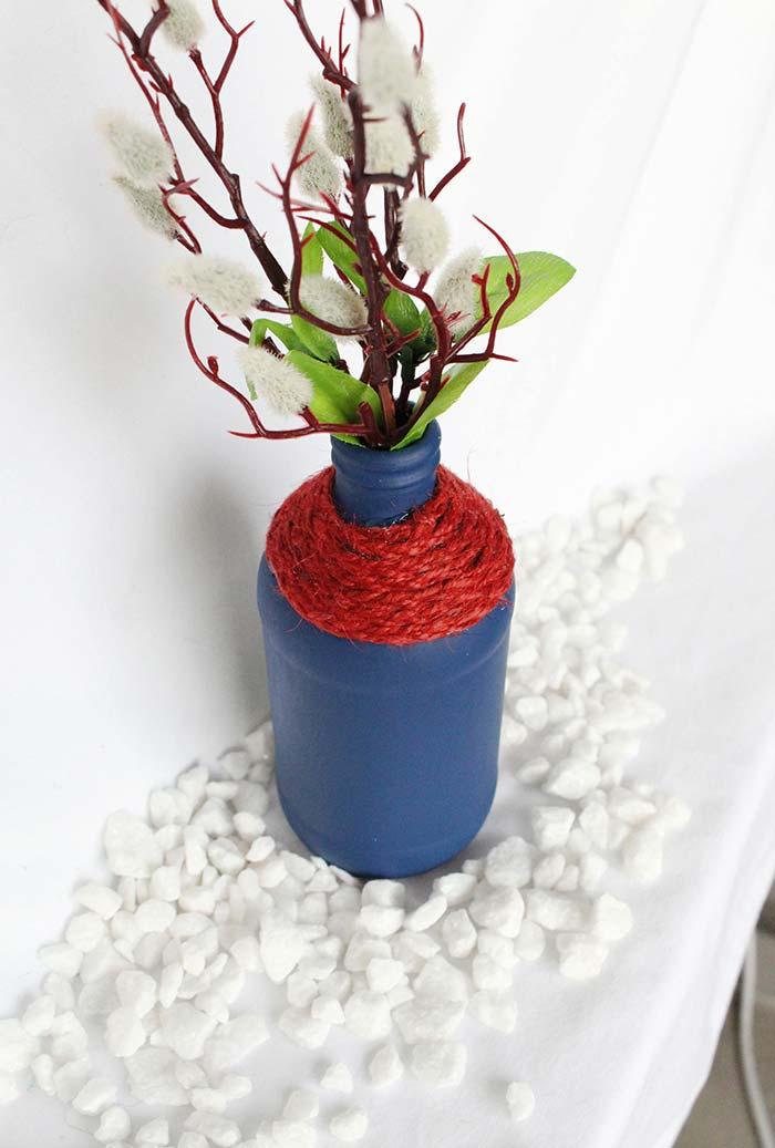 Uma cobertura em lã vermelha para finalizar a decoração da garrafa pintada de azul