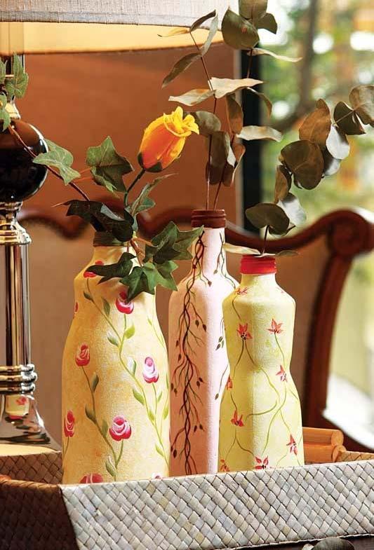 Garrafas decoradas com papel estampado cheio de flores e para servirem como vasos para outras flores