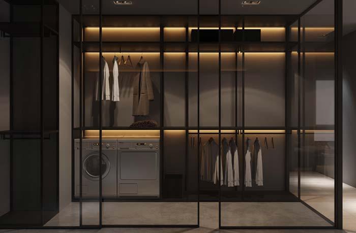 Lavanderia e modelo de closet no mesmo espaço delimitado pelas paredes de vidro