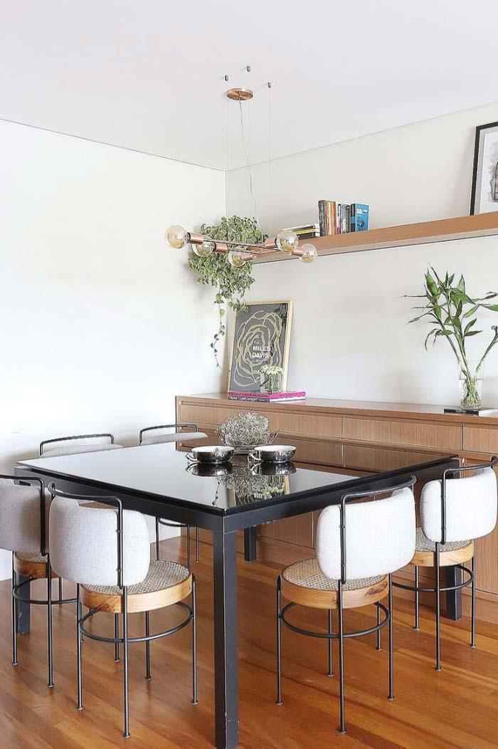 Sala de jantar decorada com mesa preta e tampo de vidro