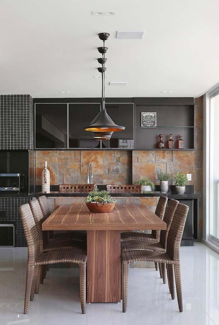Cadeiras de vime e mesa de madeira realçam a sofisticação dos armários pretos