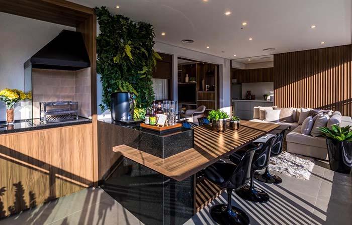 Porta de correr de madeira divide a cozinha da varanda gourmet