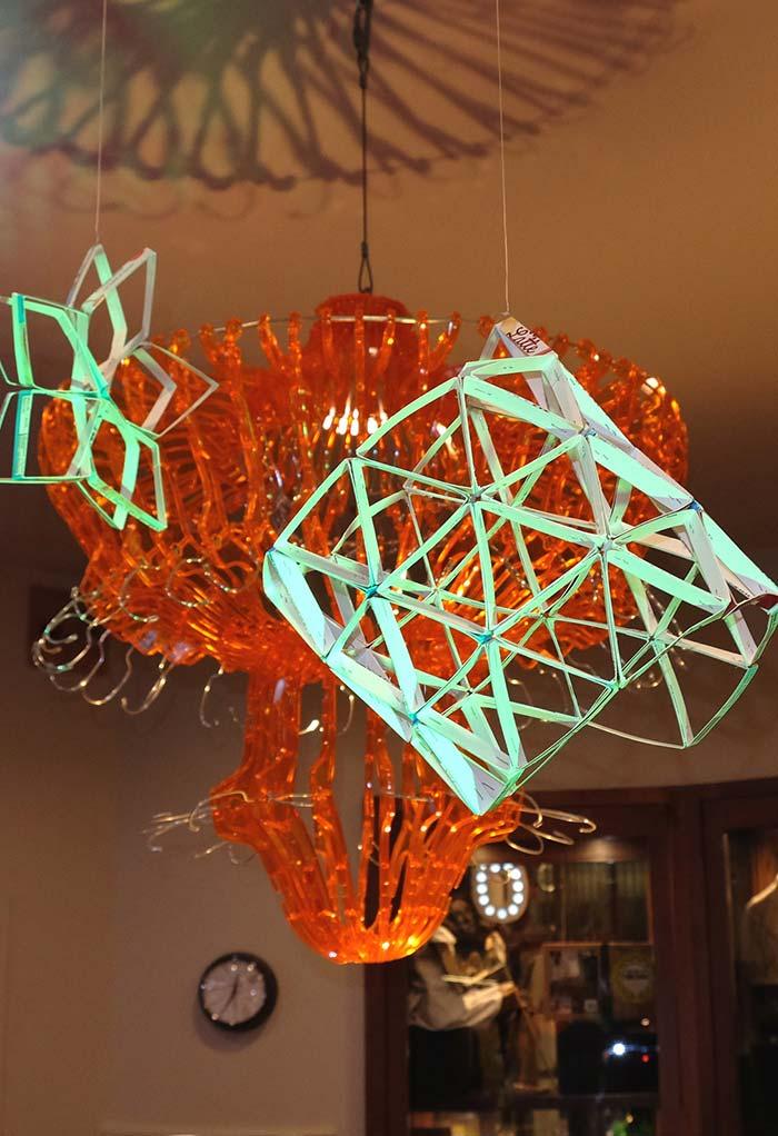 Decoração suspensa e vazada de formas geométricas feitas de artesanato com caixas de leite longa vida