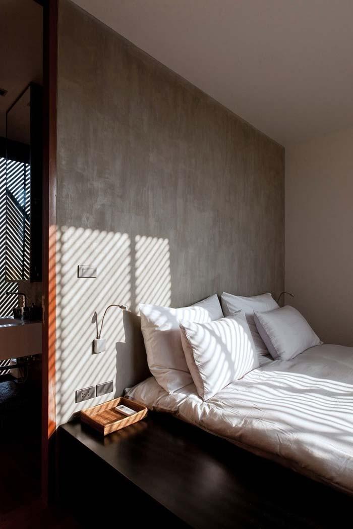 Cama japonesa em quarto com parede de cimento queimado