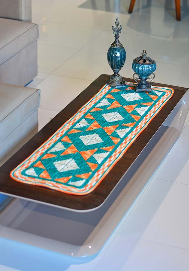 Padrão geométrico e colorido no caminho de mesa de crochê