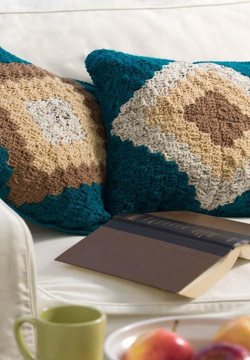 Essas almofadas de crochê coloridas com certeza deixam o sofá ainda mais confortável