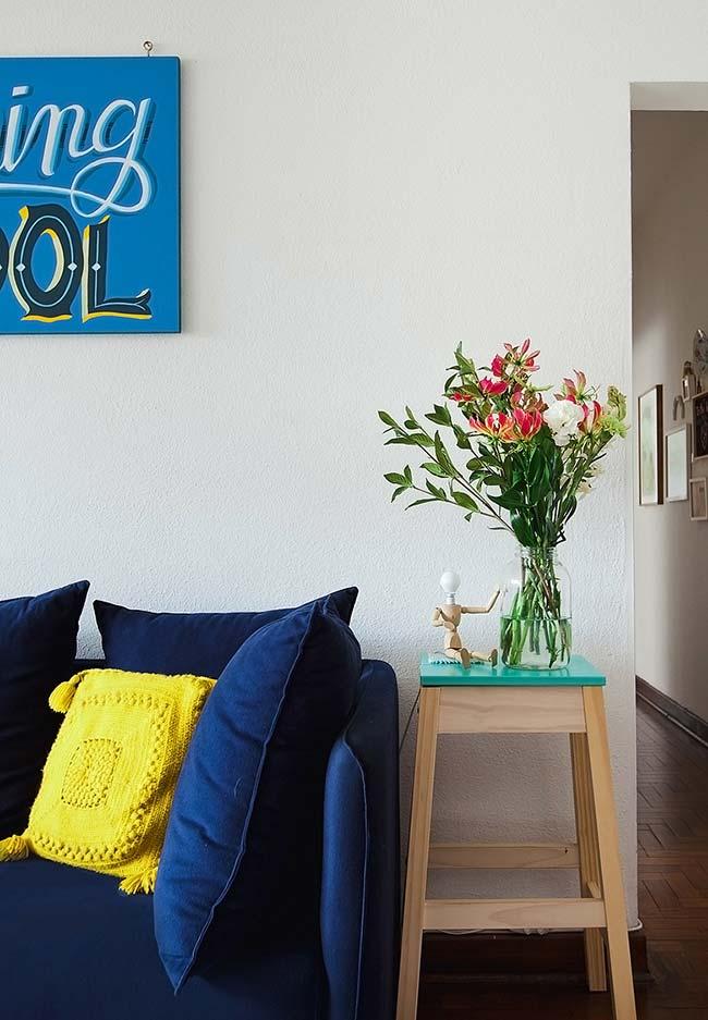 Uma almofada de crochê amarela para trazer contraste com o azul marinho do ambiente