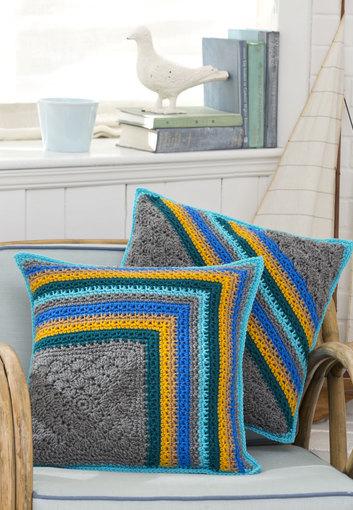 Almofada de crochê em fundo cinza com listras de cores vibrantes