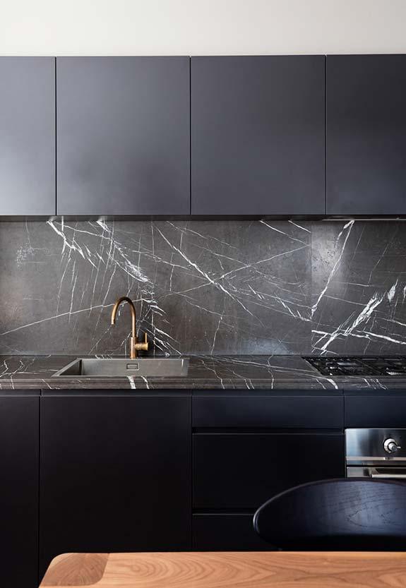 os armários pretos sem ornamentação ou puxadores externos dão uma simplicidade para o ambiente