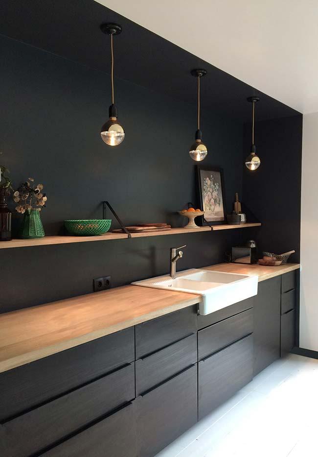 A parede que abriga os armários pretos também ganha um banho de tinta neste projeto super ligado nas tendências da decoração de ambientes
