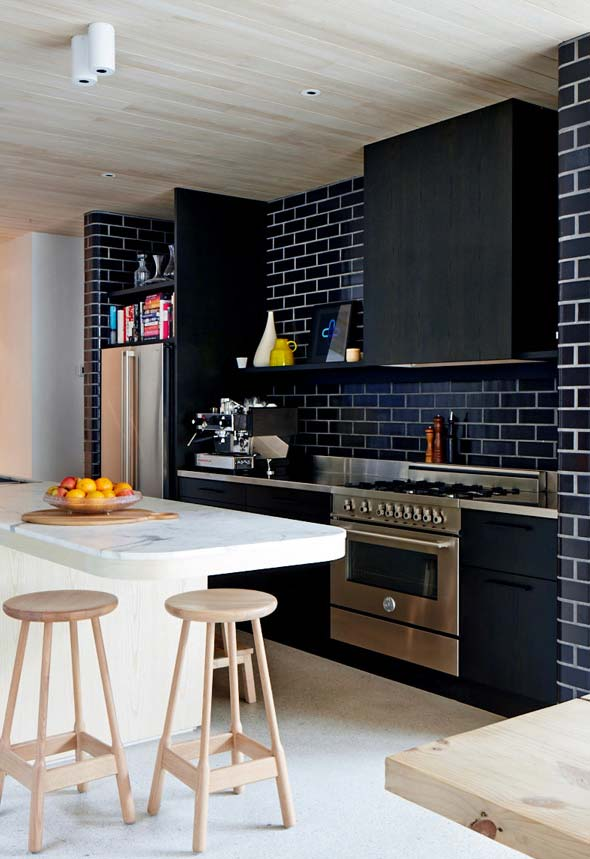Outro estilo industrial revisitado: dessa vez o revestimento de parede imita os tijolinhos em preto esmaltado