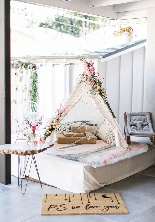 Cantinho especial para a futura mamãe: sofá com almofadas, flores e presentes para o bebê