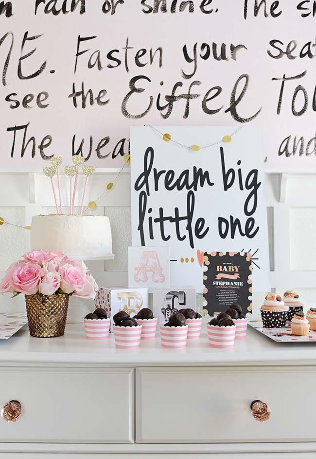 Cômoda-mesa principal para a sua celebração: um bolão, bolinhos e mensagens para o bebê