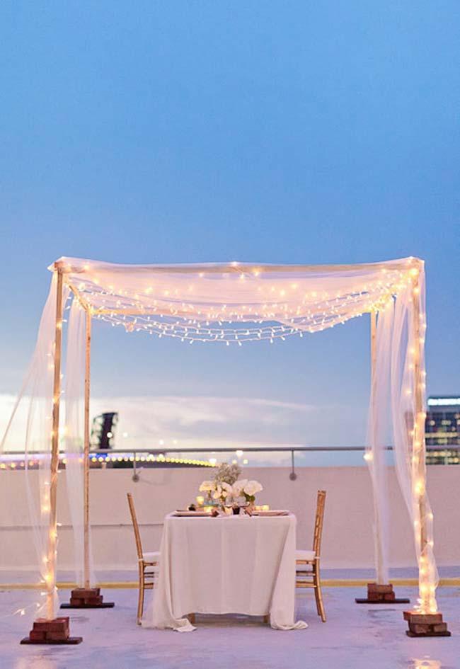 Jantar romântico ao ar livre: decoração com voil e luzes num cenário perfeito