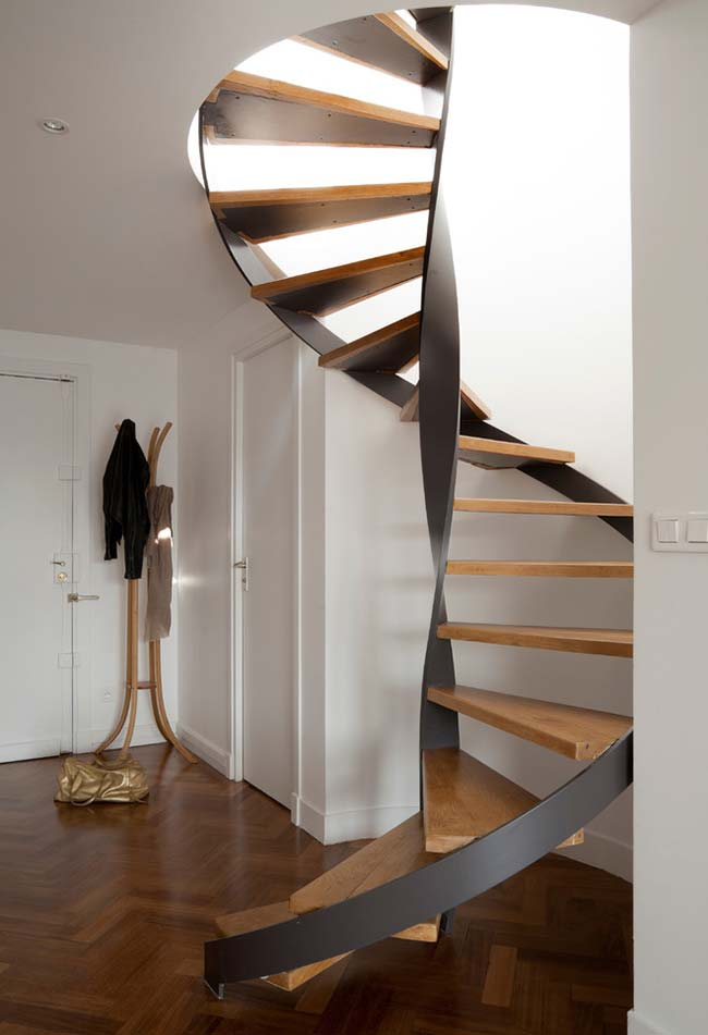 Escada caracol de madeira em corrimão que é a grande atração deste ambiente minimal