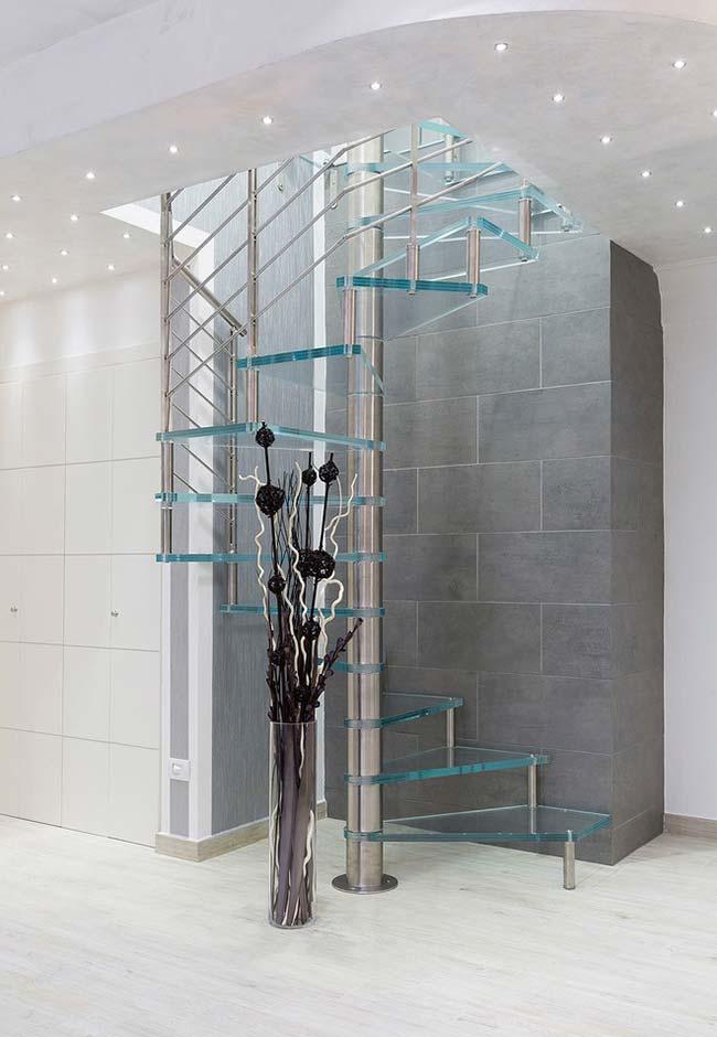 Escada caracol em aço e vidro neste ambiente elegante e super amplo