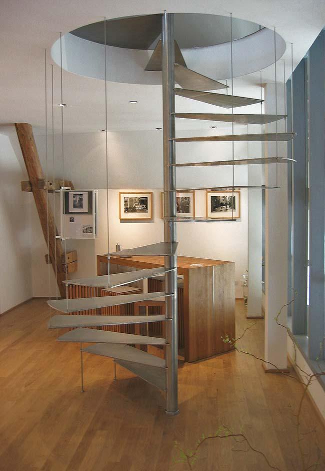Escada caracol em metal dividindo ambiente