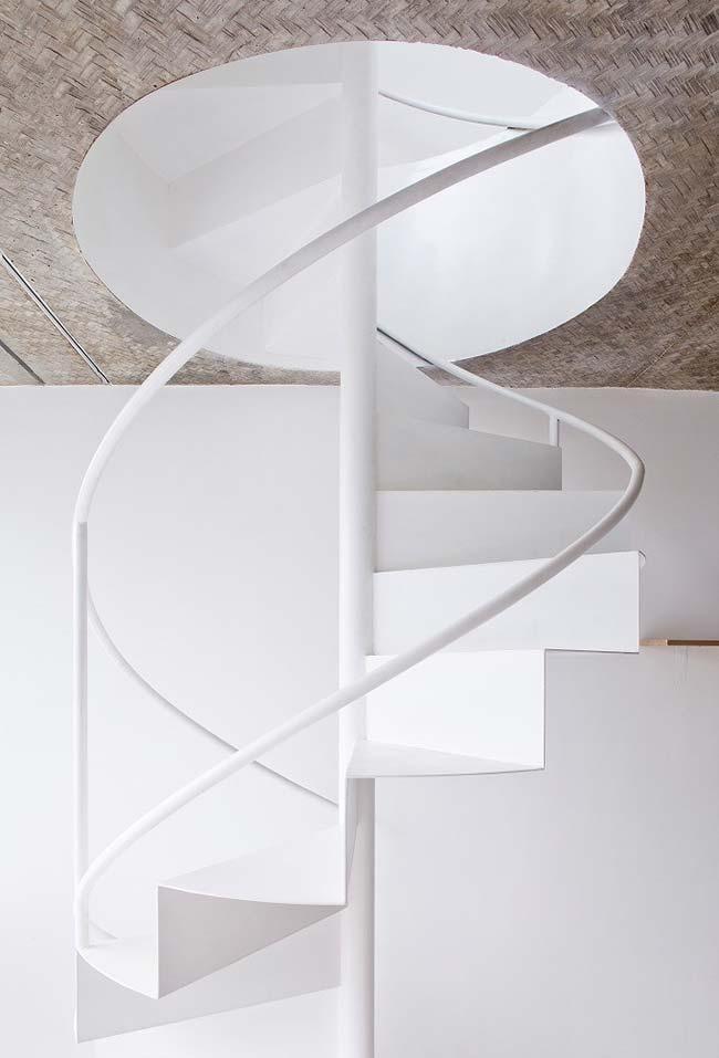 Nicho circular para escada caracol neste ambiente branco com teto decorado em madeira
