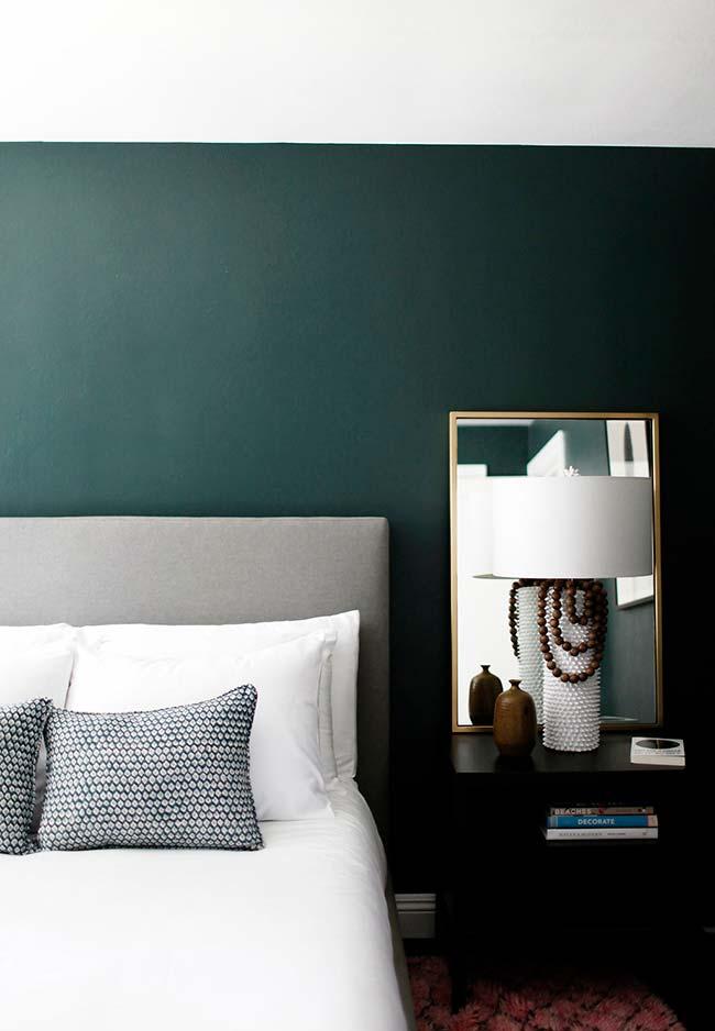 Quebra na parede escura da cama: espelho para quarto apoiado no criado-mudo reflete as paredes opostas brancas e quebra a imensidão esverdeada da parede