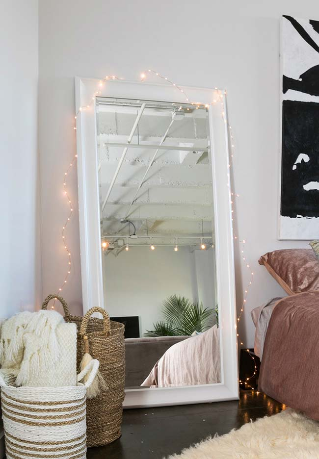 Espelho para quarto de corpo inteiro apoiado na parede e decorado com luzinhas de led