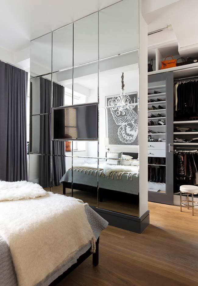 Parede espelhada na divisória de quarto de casal e closet