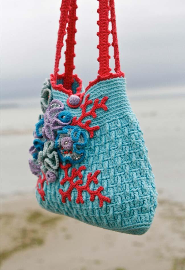 Bolsa de crochê adornada com flores e folhas coloridas