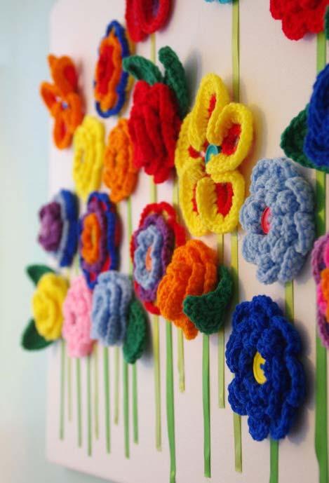 parede decorada com flores de crochê diversas e multicoloridas