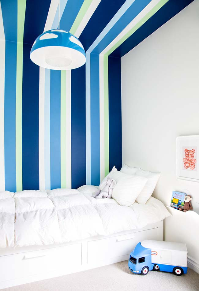 Destaque para parede da cama que, junto com o teto, ganha uma pintura em listras coloridas e super dinâmicas neste quarto infantil