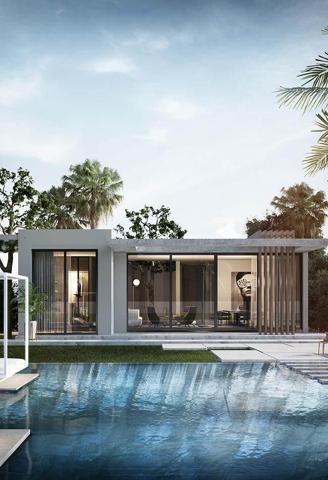 Casa com paredes de vidro optou pelo telhado embutido para valorizar a proposta clean da arquitetura