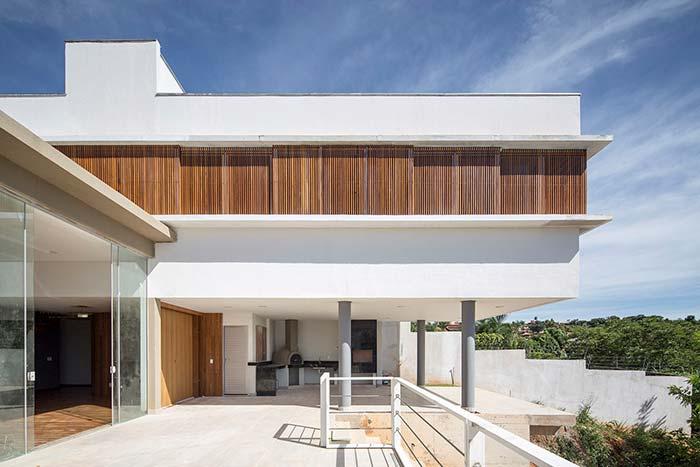 Casa branca, detalhes em madeira e telhado embutido