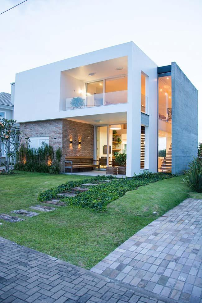 Casa moderna com telhado embutido apostou em uma fachada com diferentes materiais