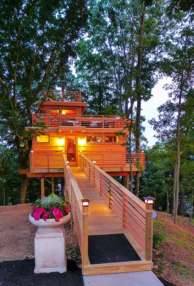 Apoiada no chão e em um complexo de árvores, essa casa na árvore ganha uma passarela e dois andares em madeira